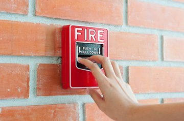 red fire alarm on wall with hand about to pull it