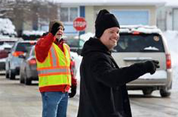 smiling adult directing traffic in carline