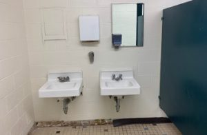 Sad-looking public bathroom showing 2 sinks, ripped up floor, mirror missing